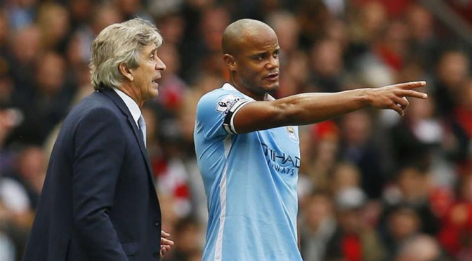 Manchester City captain Vincent Kompany chats with manager Manuel Pellegrini